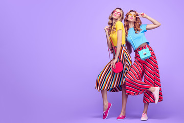 Wall Mural - Full-length portrait Two Girls with Wavy Hairstyle Having Fun Dance. Young Beautiful Pretty Model Woman in Striped Fashion Stylish Summer Outfit. Crazy Sisters Friends on Purple