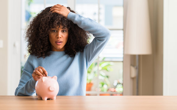 African american woman saves money in piggy bank stressed with hand on head, shocked with shame and surprise face, angry and frustrated. Fear and upset for mistake.