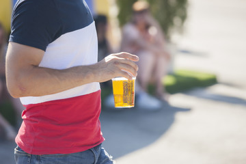 A man holding a plastic glass with beer