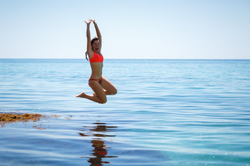 A girl is jumping into the sea water. Summer mood. Vacation at sea. Beautiful jump of a young woman in a swimsuit. Fuss and fun.