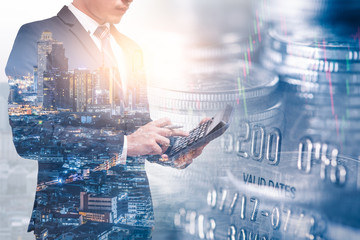 the double exposure image of businessman using a calculator overlay with cityscape and coin stack image and white copy space. the concept of accounting, business, financial, economy and investment.
