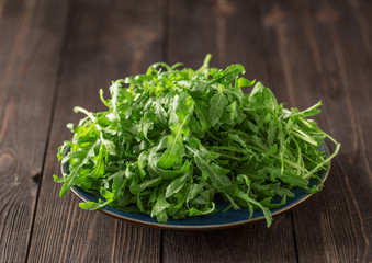 Fresh green arugula in bowl on table. Arugula rucola for salad. Close up of fresh green healthy food. Diet concept