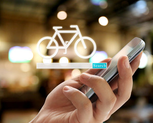 Hand of businessman holding a smartphone and have bicycle symbol to search.