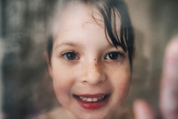 Portrait of a smiling girl looking through the wet shower glass