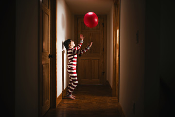 Girl standing in the hallway playing with a giant ball