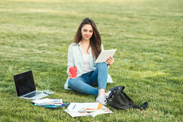 A young girl student with notebooks and a folder with headphones in her ears listening to an online lecture. She translates the text into her native language and prepares for exams Wall mural