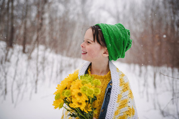 Smiling Girl standing in the snow holding a bunch of flowers