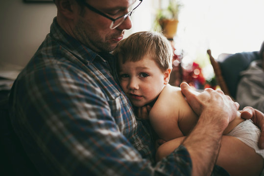 Father sitting on couch cuddling his son and kissing him on the head