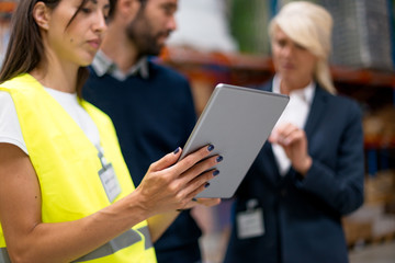 Young woman with digital tablet in warehouse