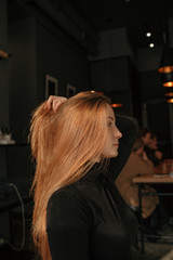 Young girl with long red hair sitting in café