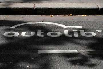 An Autolib' electric car-sharing logo is painted on the road at an Autolib' charging station in Paris