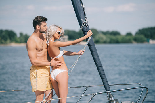 side view of beautiful young couple in swimwear hugging while standing together on yacht