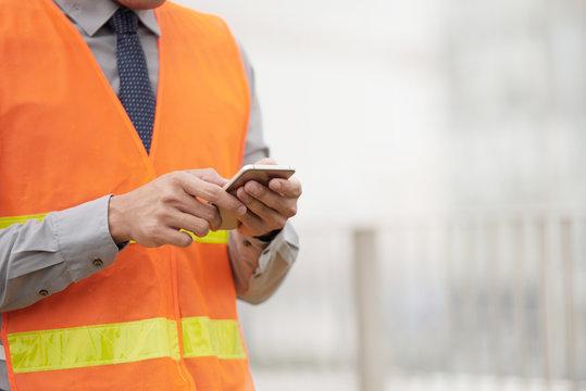 Foreman sending instructions via smartphone
