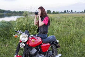 Girl sitting on a vintage motorcycle with a camera