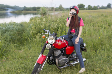 Girl in a retro helmet sitting on a vintage motorcycle with a camera