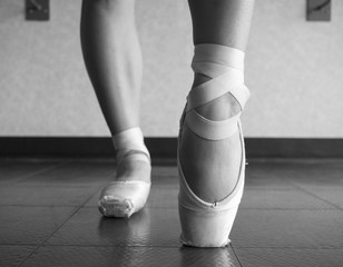 Close up view of a ballerina ballet dance, warming up her feet in ballet class with focus on her foot in her pointe shoe ballet slipper en pointe on the block