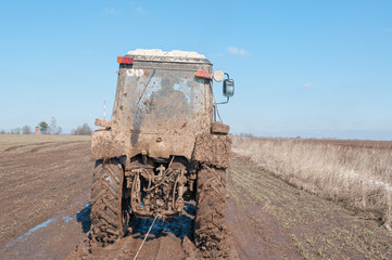 Wheeled tractor tows in mud on dirt road in fallow field