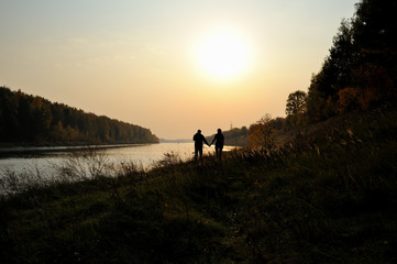 Young couple is walking along the river bank at sunset. Warm autumn evening. Silhouettes of a girl and a boy walking by the hand. Silhouettes of trees on the river bank and low setting sun in the sky.