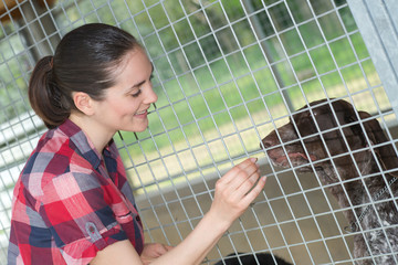 cheerful woman gives dog sweets through the fence