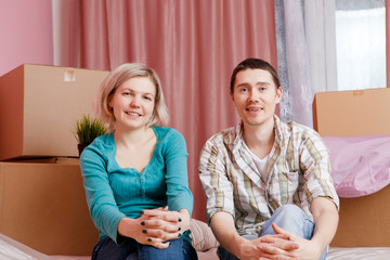 Image of happy men and women sitting on bed among cardboard boxes