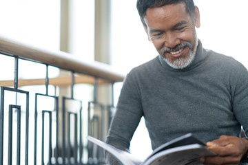 Portrait of attractive mature asian man retired with stylish short beard sitting, smiling and reading magazine books in coffee shop. Old happy handsome businessman in urban relax lifestyle concept.