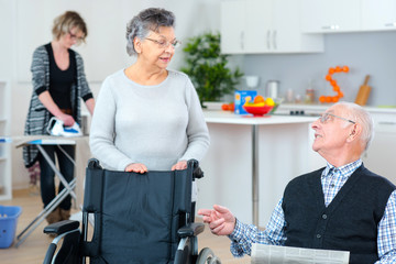 senior couple at home with carer helping out