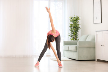 Beautiful young woman training at home in morning