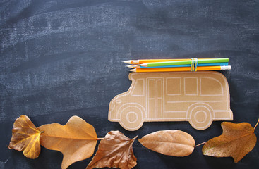 Back to school concept. Top view image school bus and pencils over autumn dry leaves classroom blackboard background.