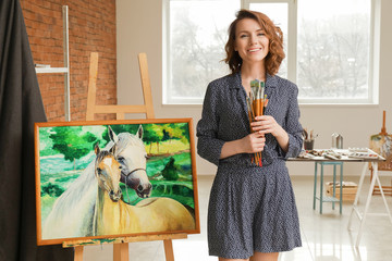 Female artist with brushes near beautiful picture in workshop