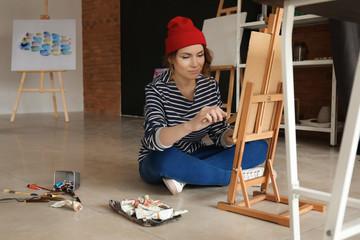 Female artist painting in workshop