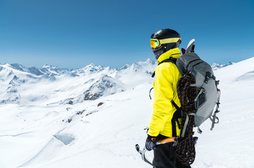 A mountaineer man holds an ice ax high in the mountains covered with snow. View from the back. outdoor extreme outdoor climbing sports using mountaineering equipment