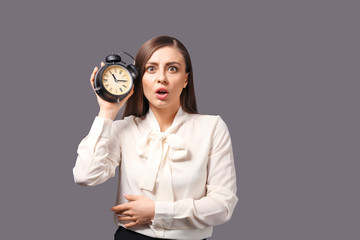 Troubled woman with alarm clock on grey background. Time management concept