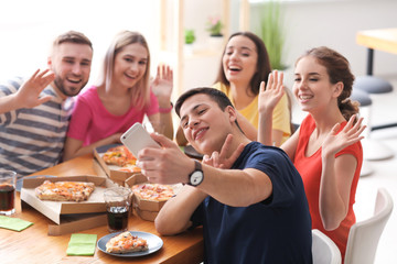 Young people with pizza taking selfie indoors