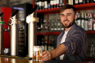 Bartender with glass of beer in bar