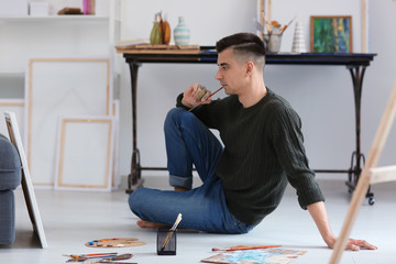Male artist waiting for inspiration in workshop