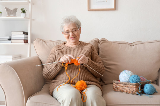 Senior woman sitting on sofa while knitting sweater at home