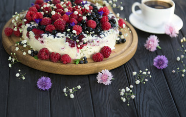 Cheese cake with currant and raspberries on a black background