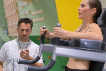 young woman execute exercise in gym motivated by coach