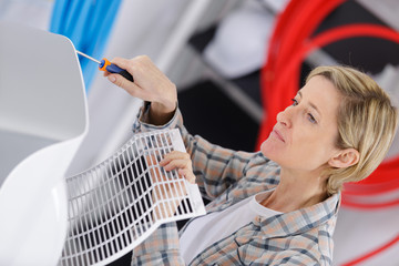 handywoman fixing air conditioner