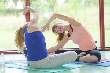 two young girls doing back bend pose in yoga class