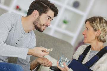 young man giving pills to an ill woman