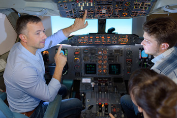 Man showing cockpit controls to young people
