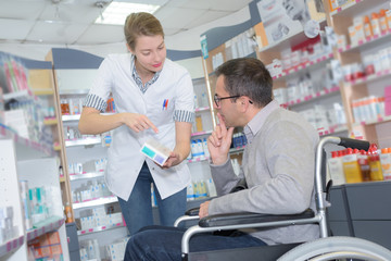 pharmacist consulting a man in a wheelchair in pharmacy