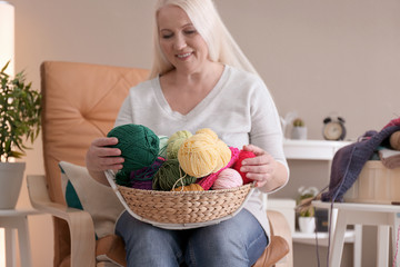 Mature woman choosing color of knitting threads indoors