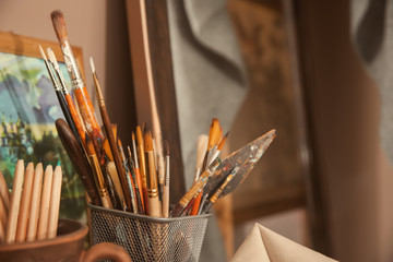 Paint tools with pencils in artist's workshop