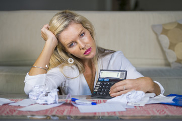 worried and desperate blond woman calculating domestic money expenses doing paperwork and bank bills accounting with calculator suffering stress