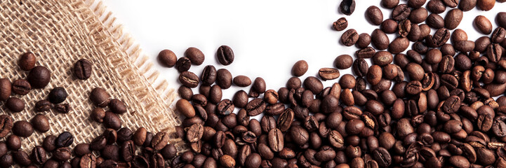 Panoramic background of roasted coffee beans on a white background with a jute sack