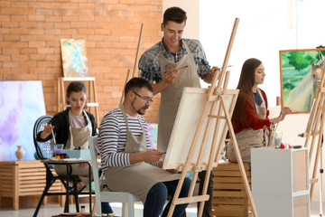 Male teacher helping his student during classes in school of painters