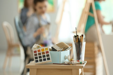 Table with paints and tools in artist's workshop