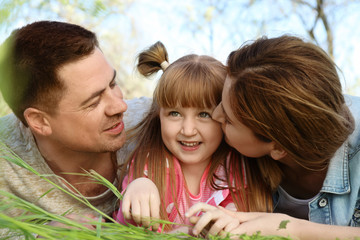 Happy family lying on green grass in park